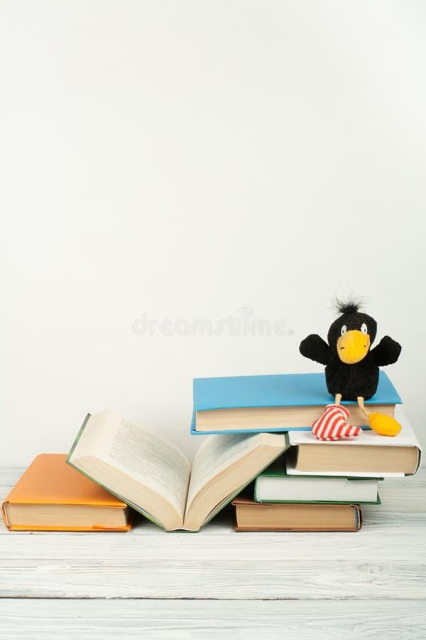 打开书,在木桌上的精装书五颜六色的书 玩具乌鸦 回到学校 复制文本的空间 教育产业 免版税库存照片