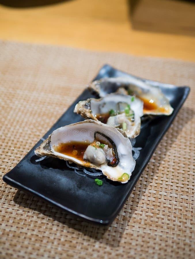打开了在黑色的盘子的新鲜的牡蛎 免版税图库摄影