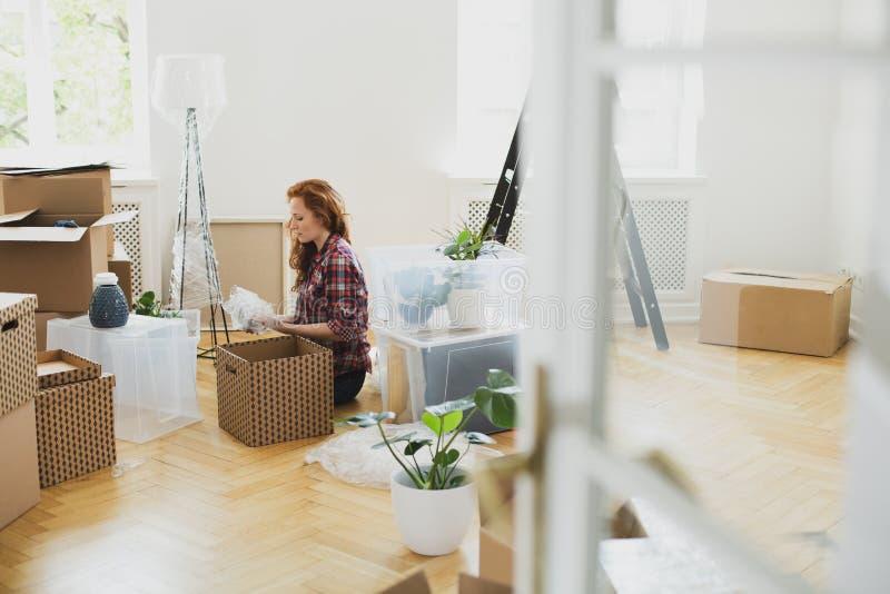 打开从纸盒箱子的妇女材料在地板上,当移动在时 免版税库存照片