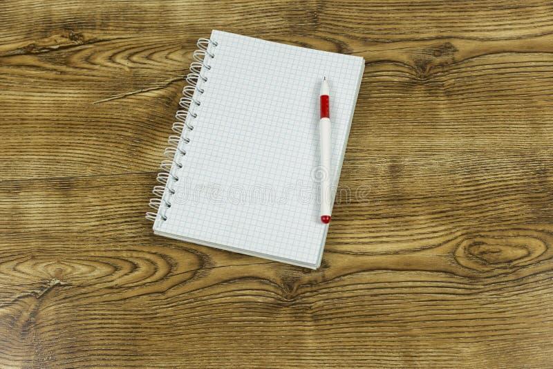 打开便条纸和笔在木纹理背景 免版税库存照片
