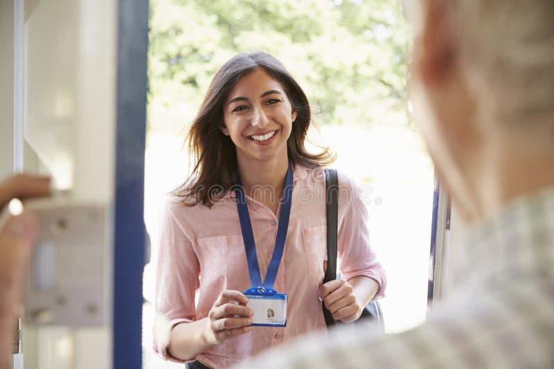 打开前门的老人对显示ID卡片的少妇 免版税图库摄影