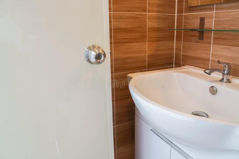 打开卫生间门洗手和面对在水池 免版税库存照片
