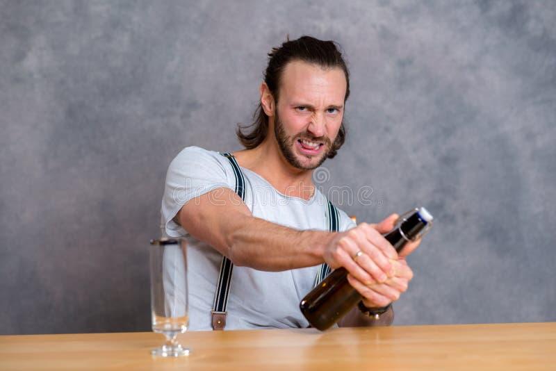 打开啤酒瓶的年轻人 免版税图库摄影