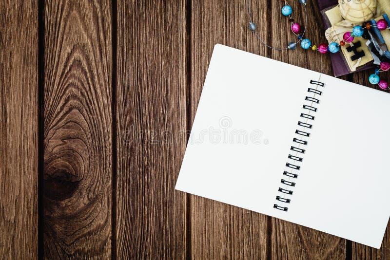 打开圆环包扎工具在木背景的笔记本与拷贝空间fo 库存图片