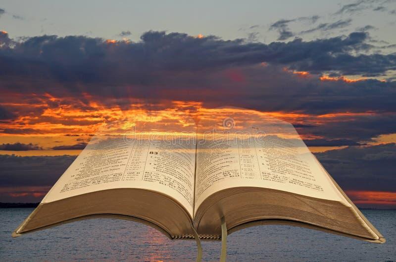 打开圣经和暴风云日落 免版税图库摄影