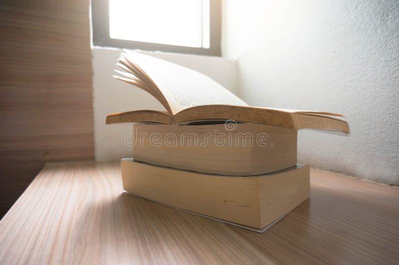 打开在一张木桌上的旧书与窗口光 皇族释放例证