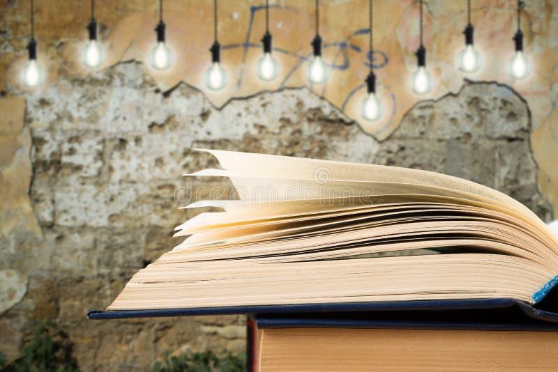 打开在书桌上的书和在背景的电灯泡 免版税库存照片