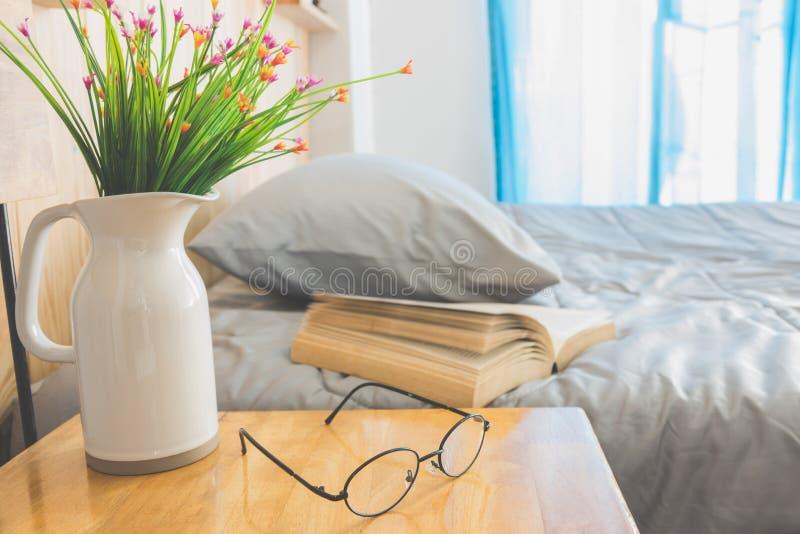 打开在床上的书与在水罐和眼睛玻璃前景的花 库存图片