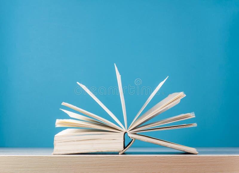 打开在木桌上的书在蓝色背景 回到学校 复制文本的空间 库存图片