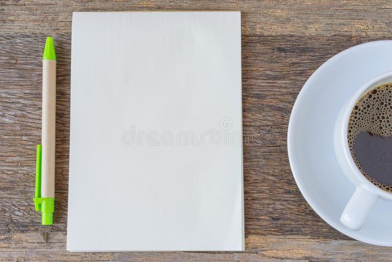 打开在木背景的笔记本与咖啡杯和笔 库存图片