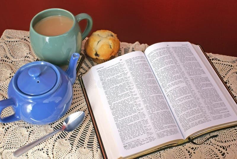 打开在桌上的圣经与葡萄酒桌布、茶壶、杯子和mu 免版税图库摄影