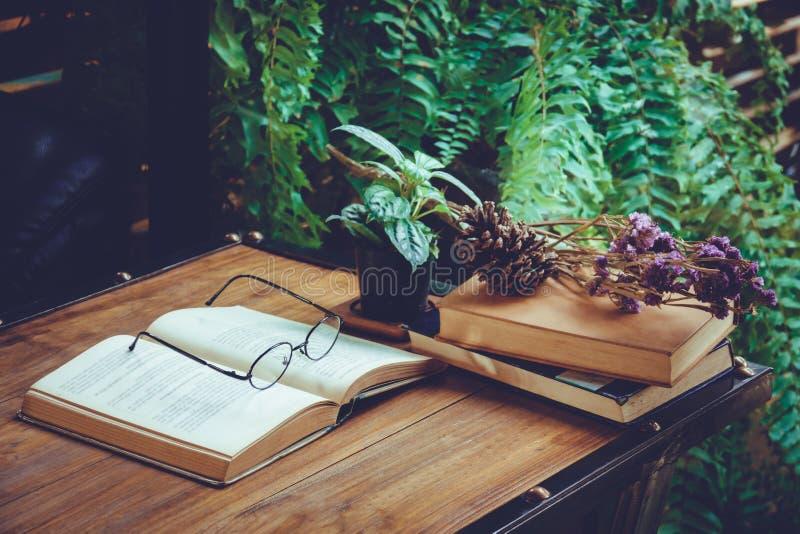 打开在桌上的旧书与在咖啡馆的干花 免版税图库摄影