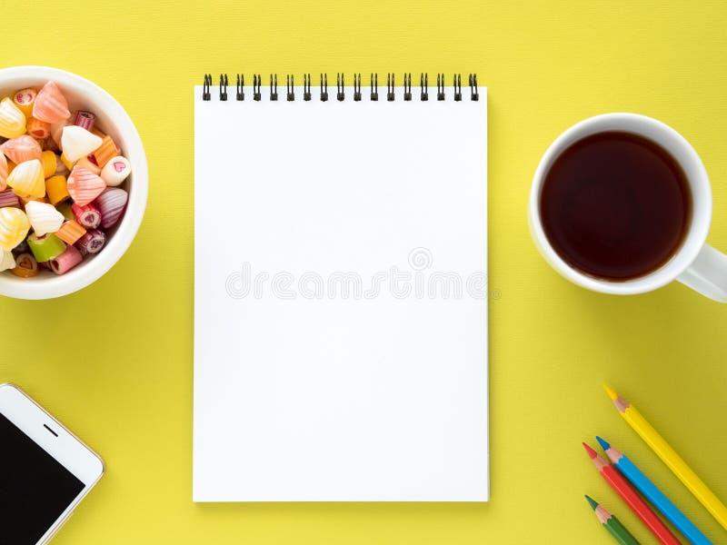 打开在螺旋的笔记薄与一张干净的白页、一杯用茶,焦糖在碗,智能手机和颜色铅笔 图库摄影