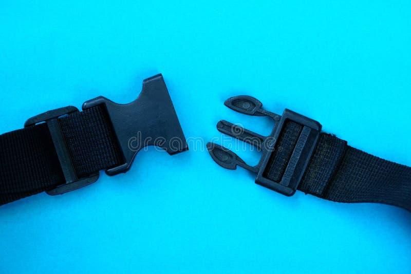 打开在鞔具的黑塑料carabiner在蓝色背景 免版税图库摄影