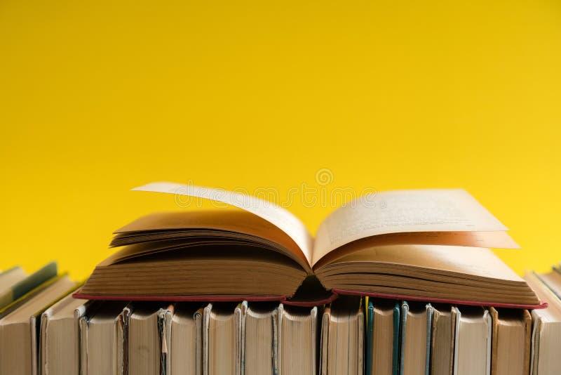 打开在黄色背景,在木桌上的精装书书的书 免版税库存图片