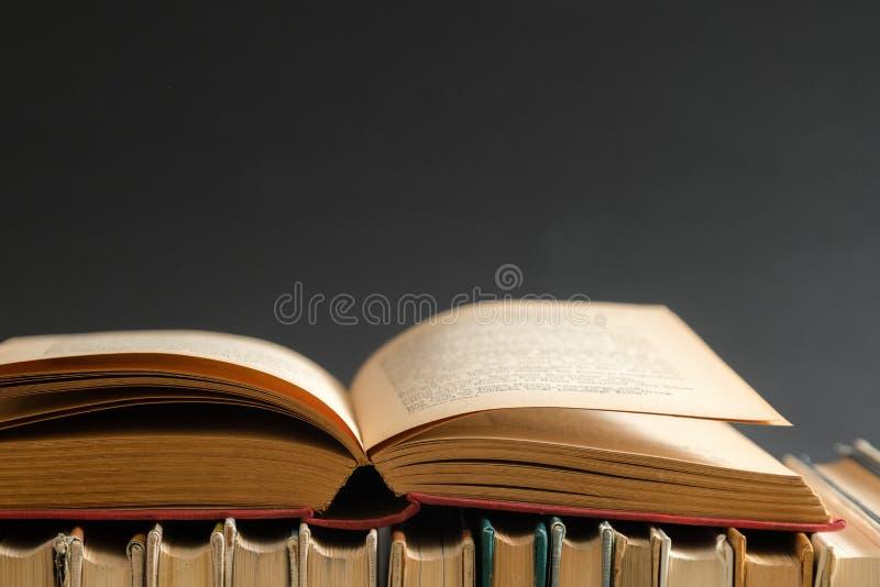 打开在黑背景,在木桌上的精装书书的书 e 库存照片
