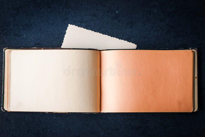 打开在黑暗的石桌上的空的葡萄酒笔记本 库存图片