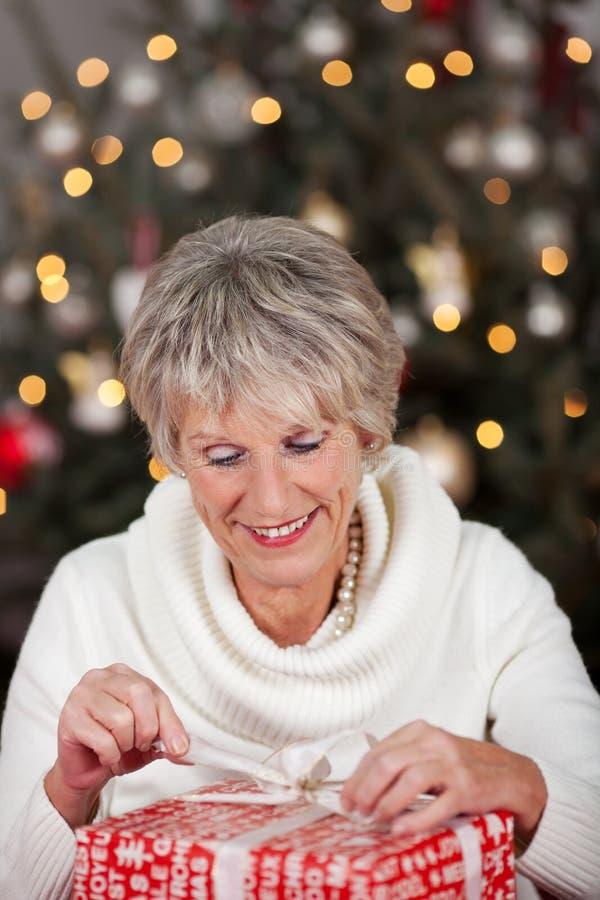打开她的圣诞节礼物的资深夫人 免版税库存照片