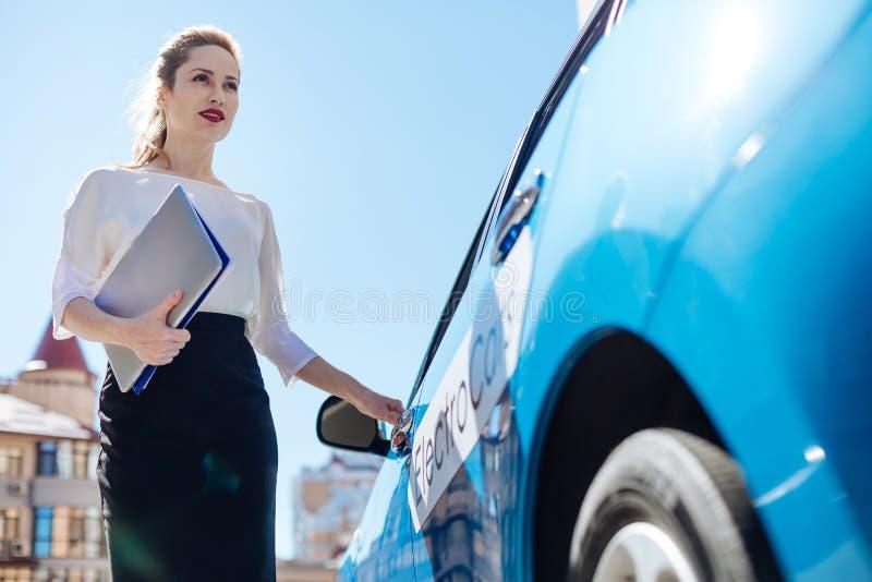 打开她的汽车的可爱的确信的女实业家 免版税图库摄影