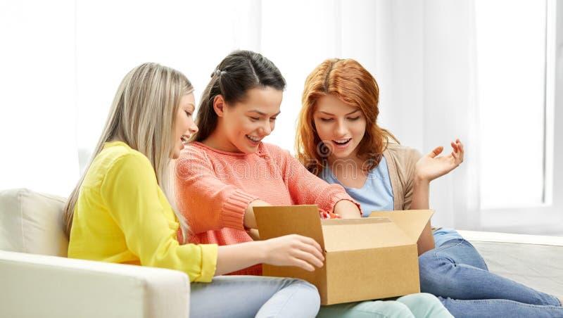 打开小包箱子的十几岁的女孩或朋友 库存照片