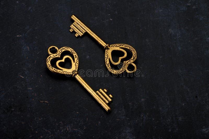 打开我的心脏-两把心形的金黄葡萄酒钥匙 库存图片
