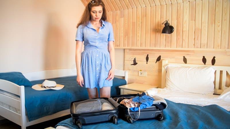 打开手提箱的美丽的少妇在旅馆客房 库存图片