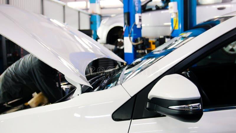 打开敞篷车引擎,电池,注射器-工作在汽车服务的技工 免版税库存图片