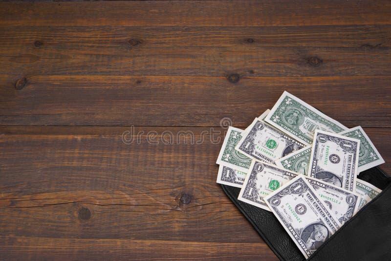 打开有一美金的男性黑皮革钱包 免版税图库摄影