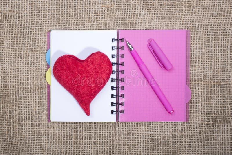 打开有圆珠笔和羊毛的红色心脏的笔记本在粗麻布背景的 库存图片