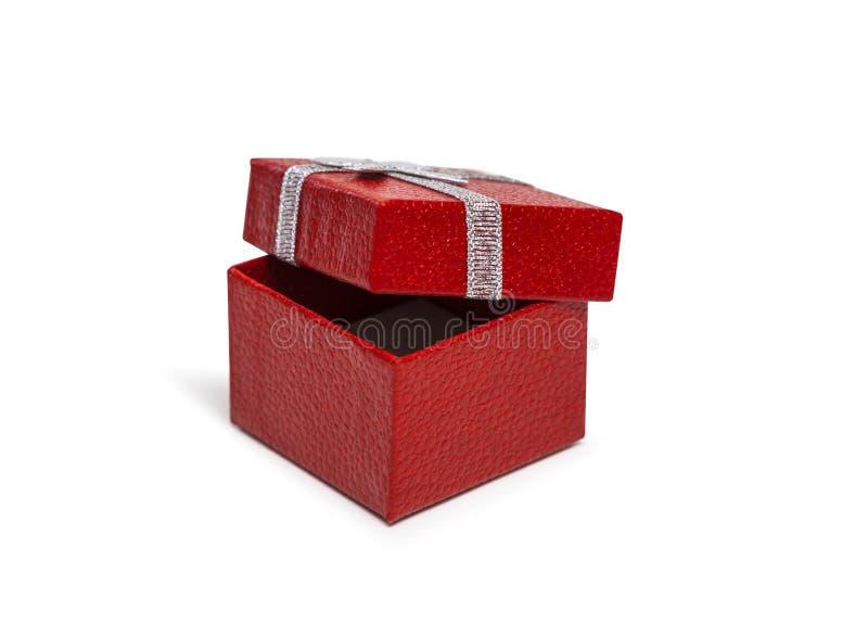 打开有在白色backgroun隔绝的银色丝带的红色礼物盒 库存照片