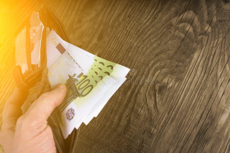 打开有数百的钱包在男性手上 免版税库存图片