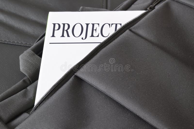 打开有有些文件的公文包在它 与对此写的标题项目的一张纸 免版税库存照片
