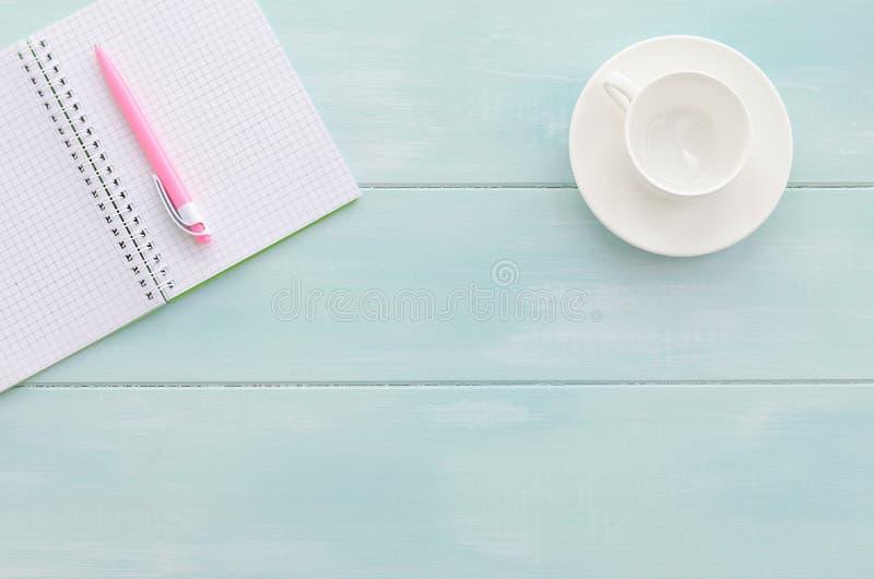 打开有桃红色笔和咖啡杯的笔记本 免版税库存照片