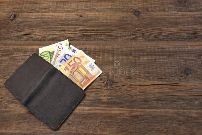 打开有欧洲票据的男性黑皮革钱包在木头 免版税图库摄影