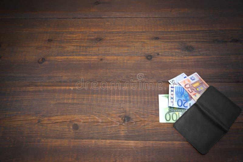 打开有欧洲票据的男性黑皮革钱包在木头 图库摄影