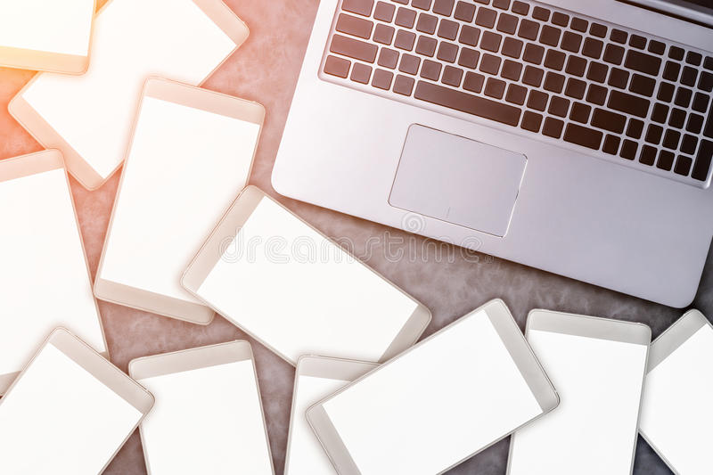 打开有白色智能手机的膝上型计算机 所有屏幕是白色的在灰色 库存图片