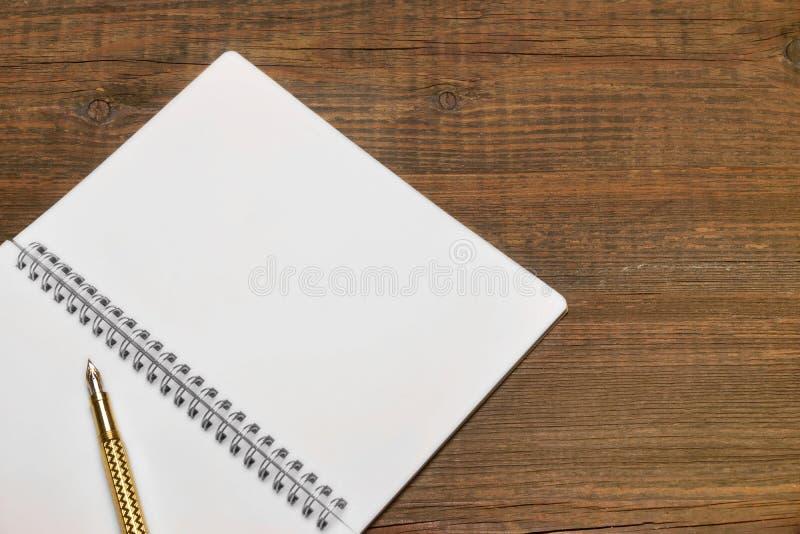 打开有白页和金笔的螺旋装订的笔记本 库存照片