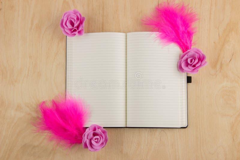 打开有白页的笔记本和在一个木选项的桃红色羽毛 免版税库存图片