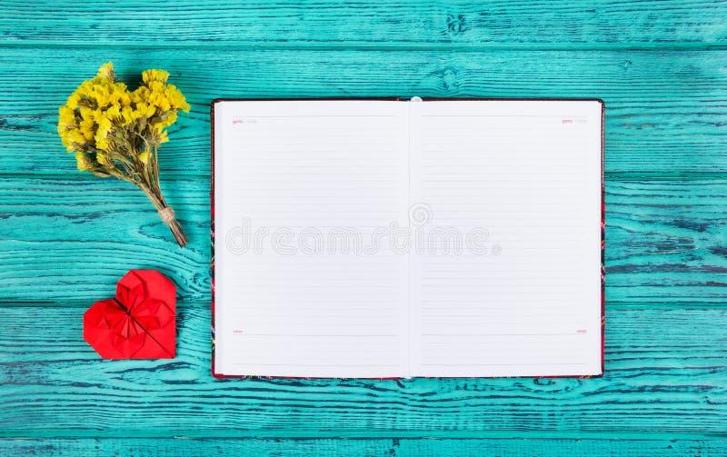 打开有空白页和origami的红色心脏的笔记本 复制空间 免版税图库摄影