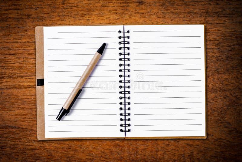 打开有笔的笔记本在木背景 免版税库存照片