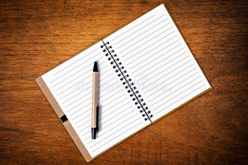 打开有笔的笔记本在木背景 库存图片