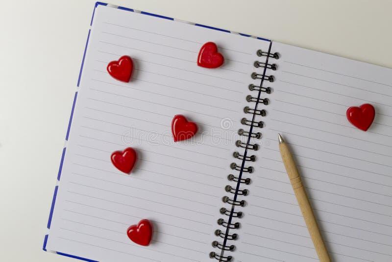 打开有红色心脏和笔的笔记本 图库摄影