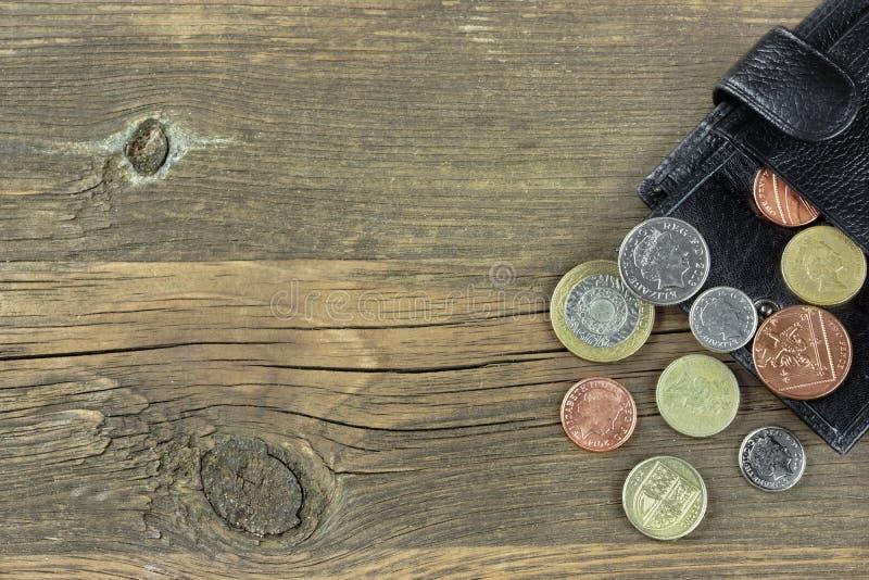 打开有英国不同的硬币的男性黑皮革钱包 免版税库存图片