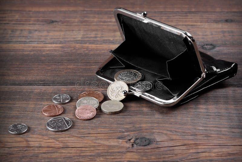 打开有英国不同的硬币的男性黑皮革钱包 库存图片