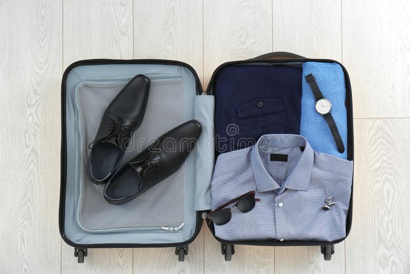 打开有衣物、鞋子和辅助部件的手提箱 免版税库存照片