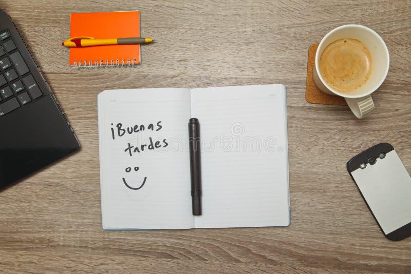 打开有西班牙人词` Buenas Tardes `你好的笔记本和一杯咖啡在木背景的 库存图片