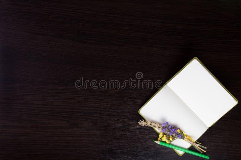 打开有钮扣眼上插的花的笔记本和在黑暗的木背景的角落的绿色铅笔图片