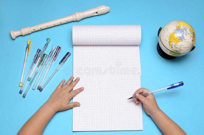 打开有长笛、地球、白种人女孩的秋叶和手的笔记本 库存图片