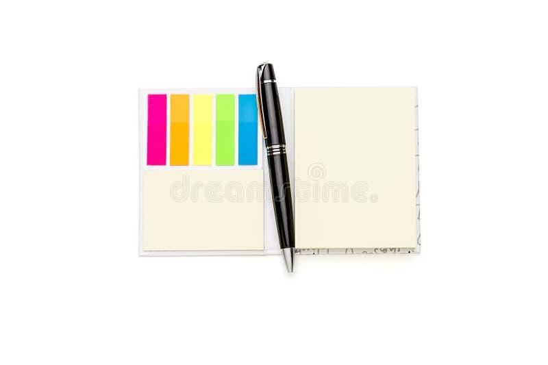 打开有颜色壁虱笔记和圆珠笔的空白的垫 库存图片