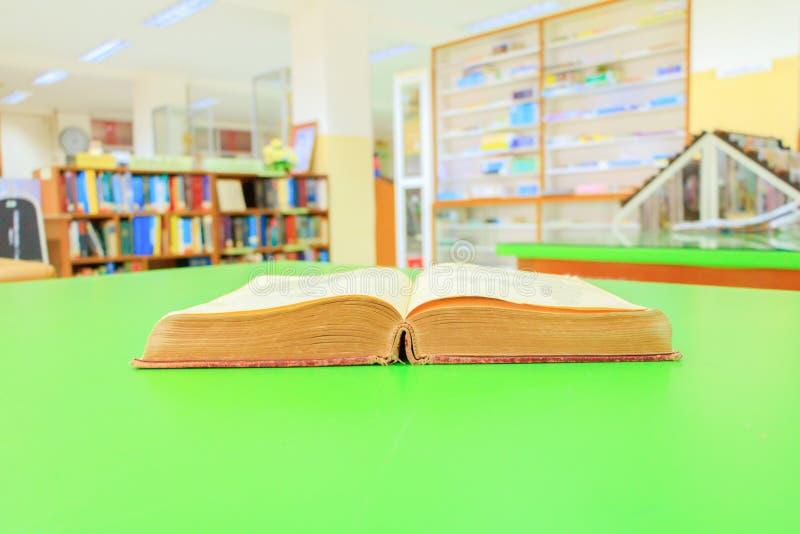 打开桌绿色迷离书架背景的旧书内部图书馆学校 免版税库存照片